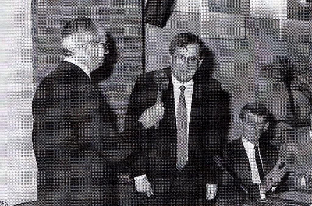 Loco-burgemeester G. Driessen overhandigt de voorzittershamer aan Romé Fasol bij diens installatie tot burgemeester van Horst op z8 mei 1988. Rechts gemeentesecretaris B. Oolthuis. (foto: gemeente Horst)