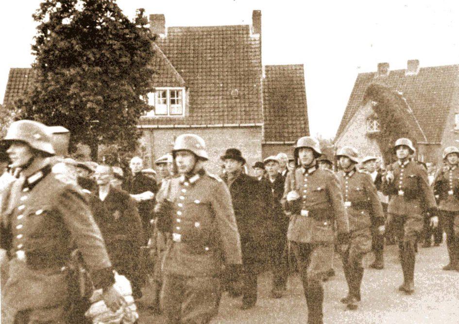 Mannen onder begeleiding van Duitse soldaten op weg naar Venlo voor transport per trein naar Duitsland. (Foto: oosnaer.nl)